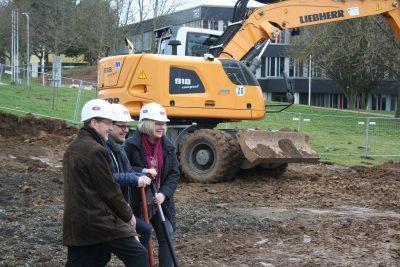 Spatenstich mit (v.l.) Peter Hammerschmidt, Wolfgang Schäfer, Silke Engler und schwerem Gerät im Hintergrund