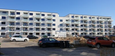 Freies Grundstück mit der Wohnanlage der HWG – Baunatal im Hintergrund.